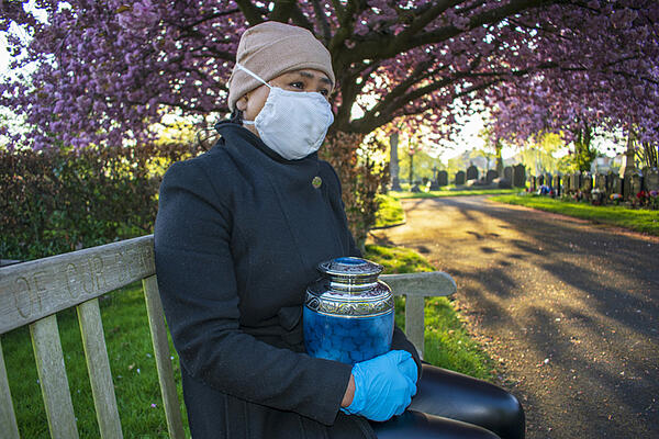 woman wearing mask and holding cremation urn
